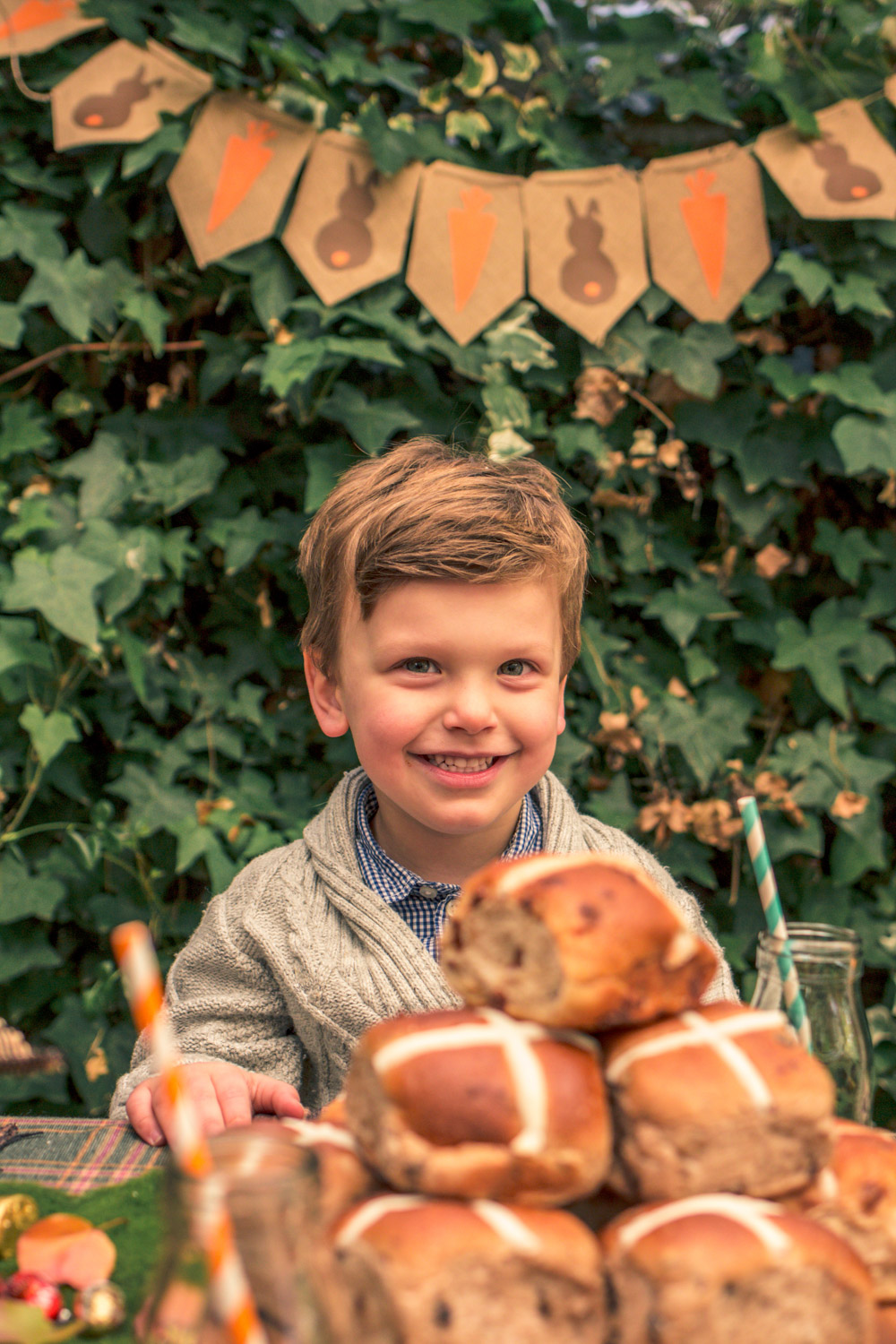 Little boy eating hot cross buns at kids party table at Autumn easter egg hunt