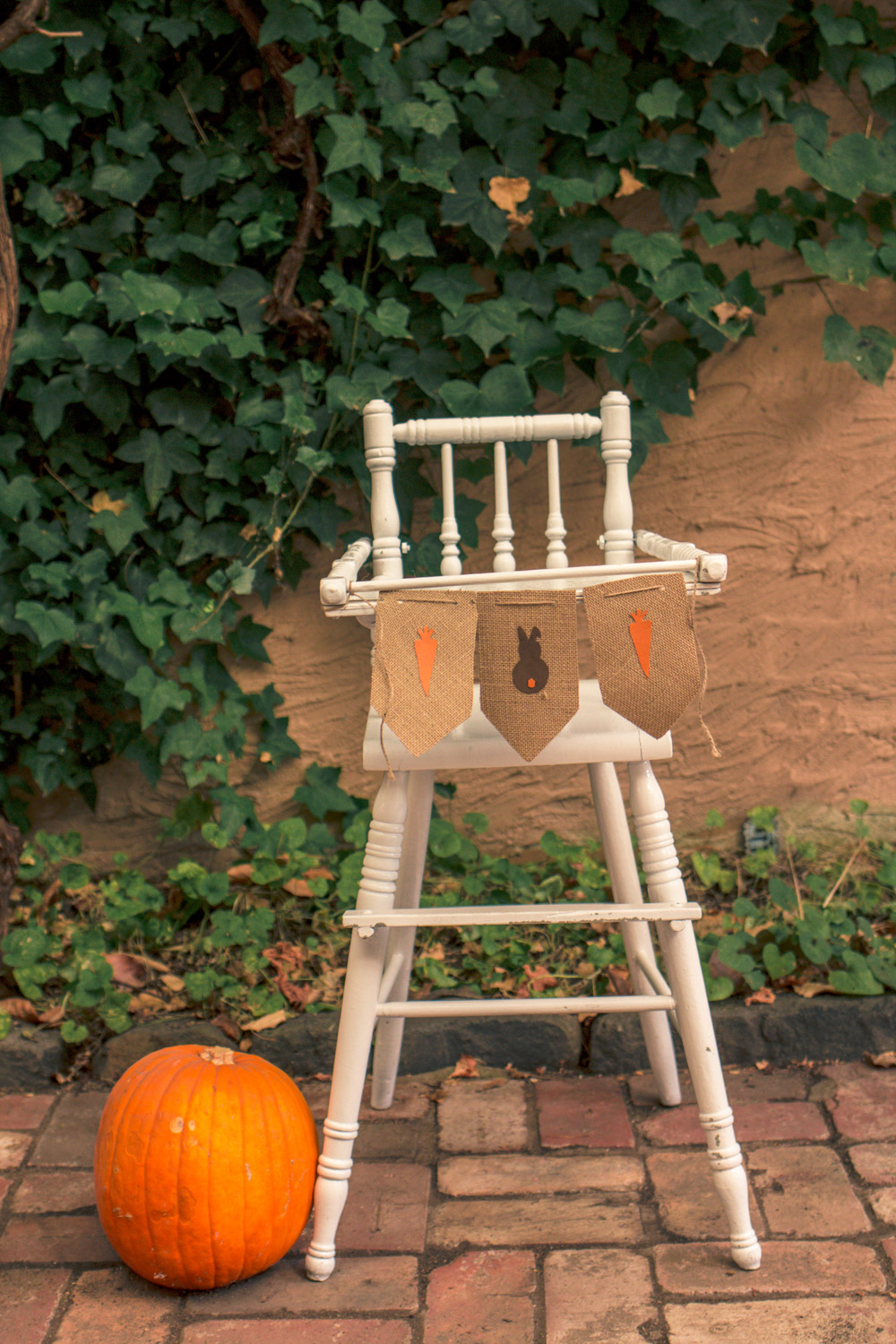 Vintage painted baby high chair decorated for autumn easter egg hunt with bunting, carrots and pumpkins