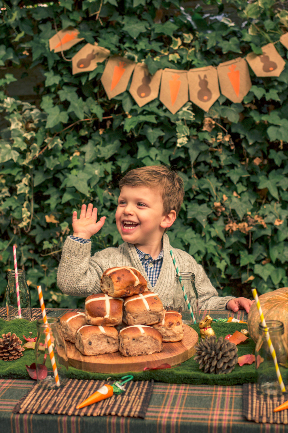 Little boy in Janie and Jack knit cardigan sitting at the kids party table at the Autumn easter egg hunt with hot cross buns and pumpkins and pine cones sitting below autumn themes easter bunting