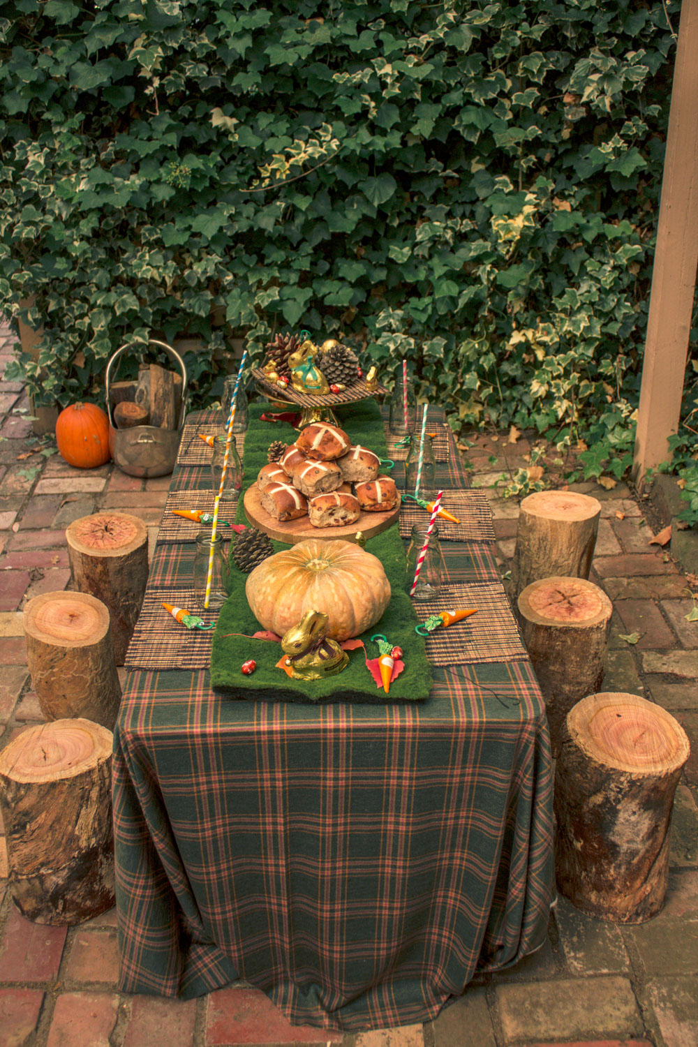 Children easter table for autumn themed easter egg hunt. Table decorated with pumpkins, hot cross buns, pine cones and chocolate carrots and wooden log stools
