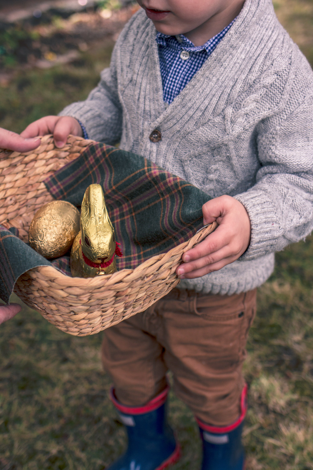Little boy in vintage knitwear holding a basket of chocolates at Goldfields Girl Autumn Easter Egg Hunt