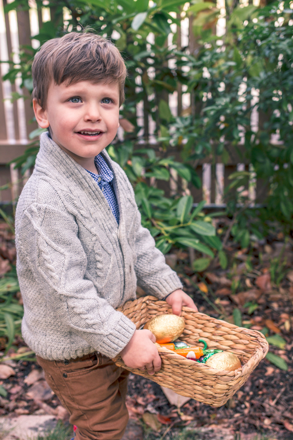 Toddler wearing Janie and Jack Knit Cardigan at Autumn Easter Egg Hunt holding a basket of chocolate eggs and carrots