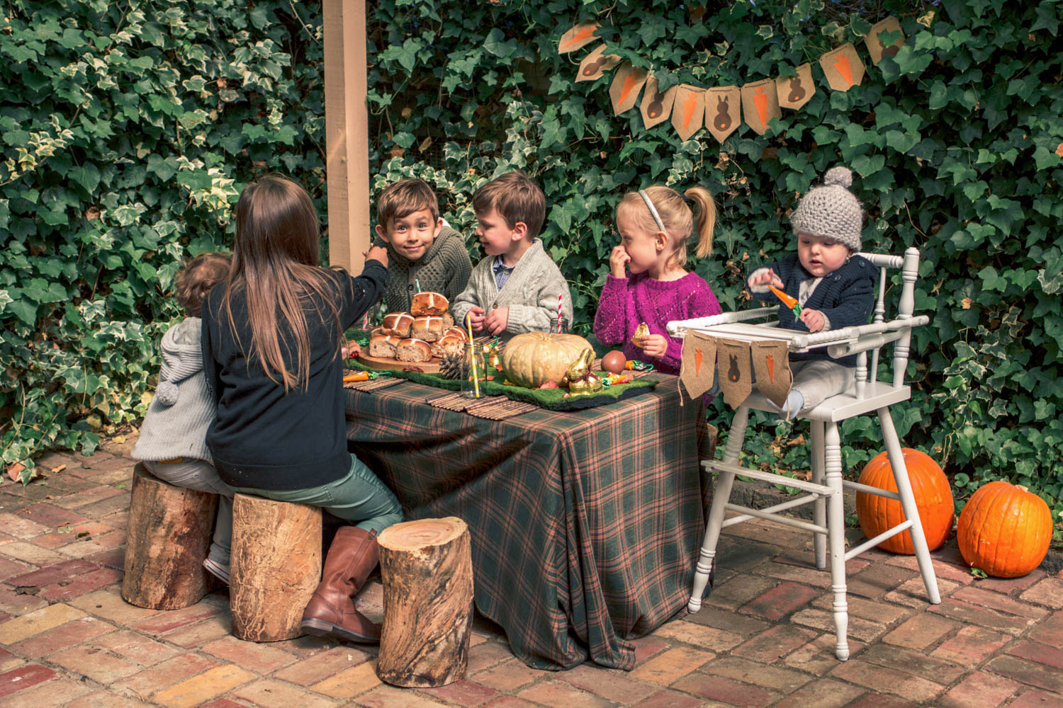 Children seated on wooden logs easting hot cross buns and chocolates at party table for autumn easter egg hunt. Baby seated in vintage wooden high chair with bunting