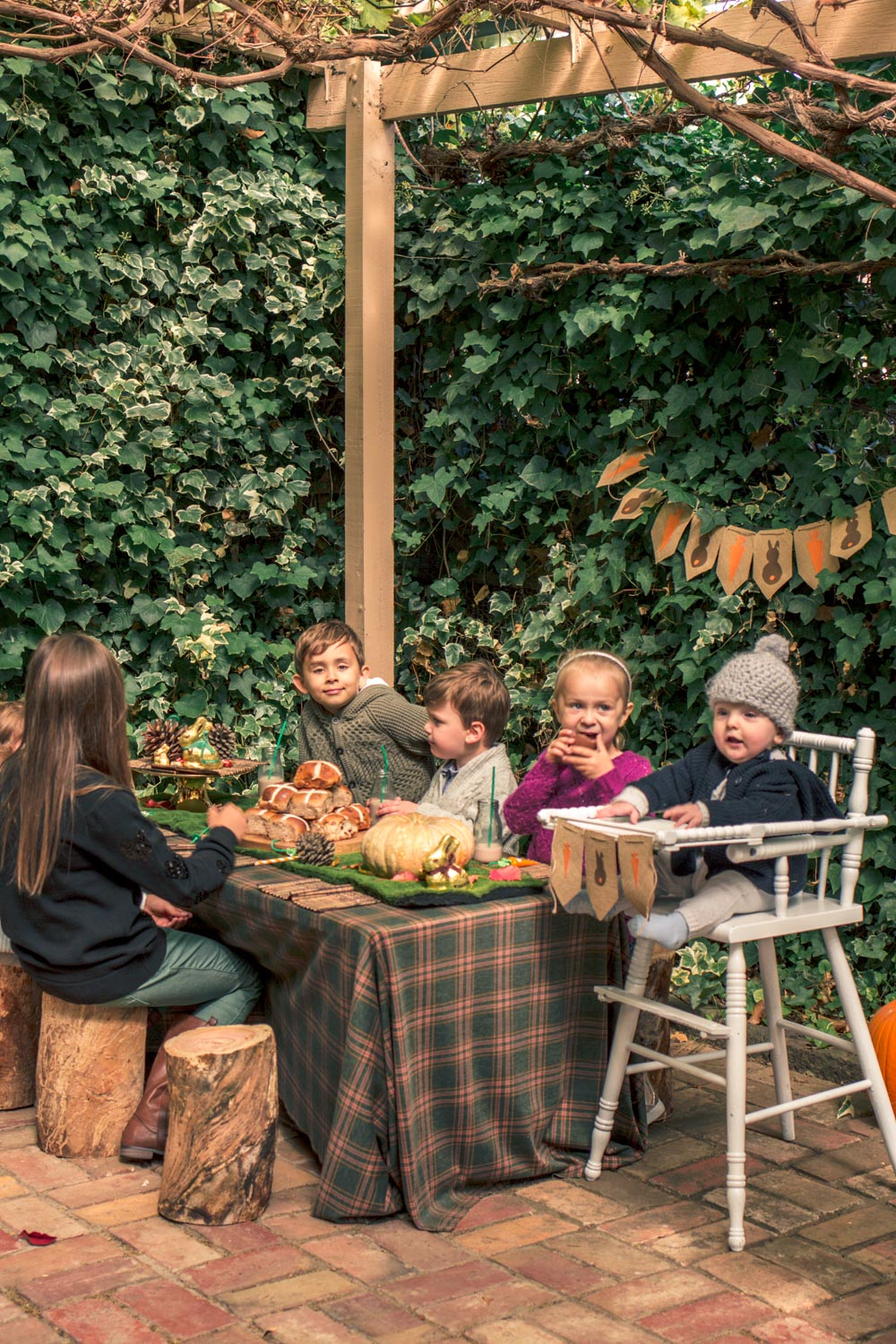 Kids seated at children party table for autumn easter breakfast at autumn easter egg hunt. Table decorated with woodland themed pine cones, pumpkins, chocolates and hot cross buns.