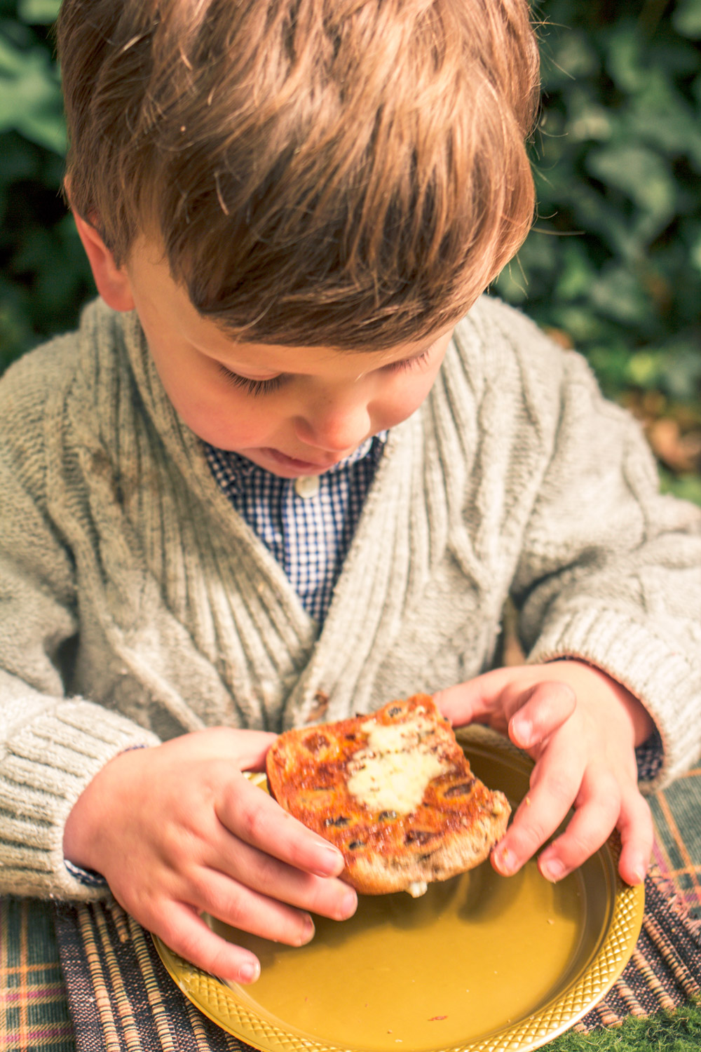Little boy in knit cardigan eating a hot cross bun at easter table
