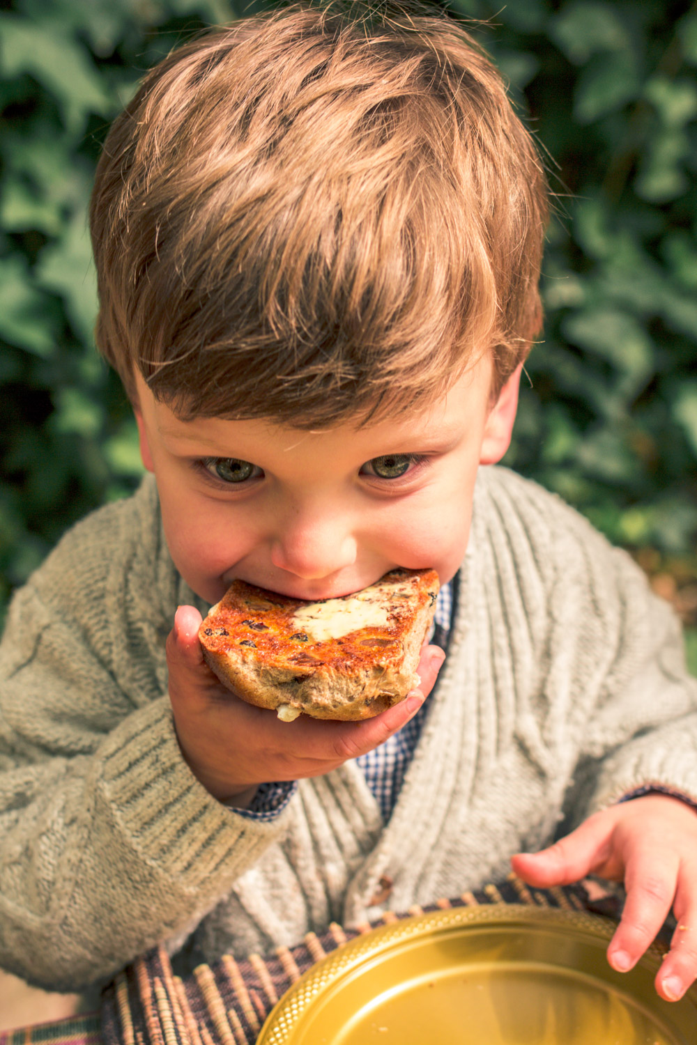 Little boy wearing a knit cardigan eating a Bakers Delight Hot Cross Bun at Autumn Easter Egg Hunt