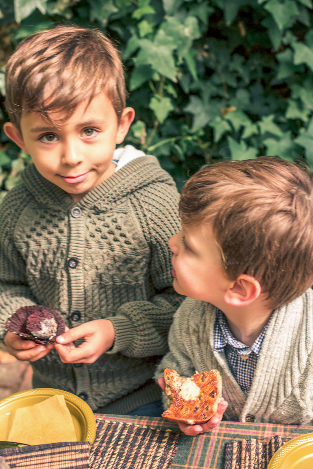 Little boys dressed in knit cardigans eating hot cross buns at autumn easter egg hunt party