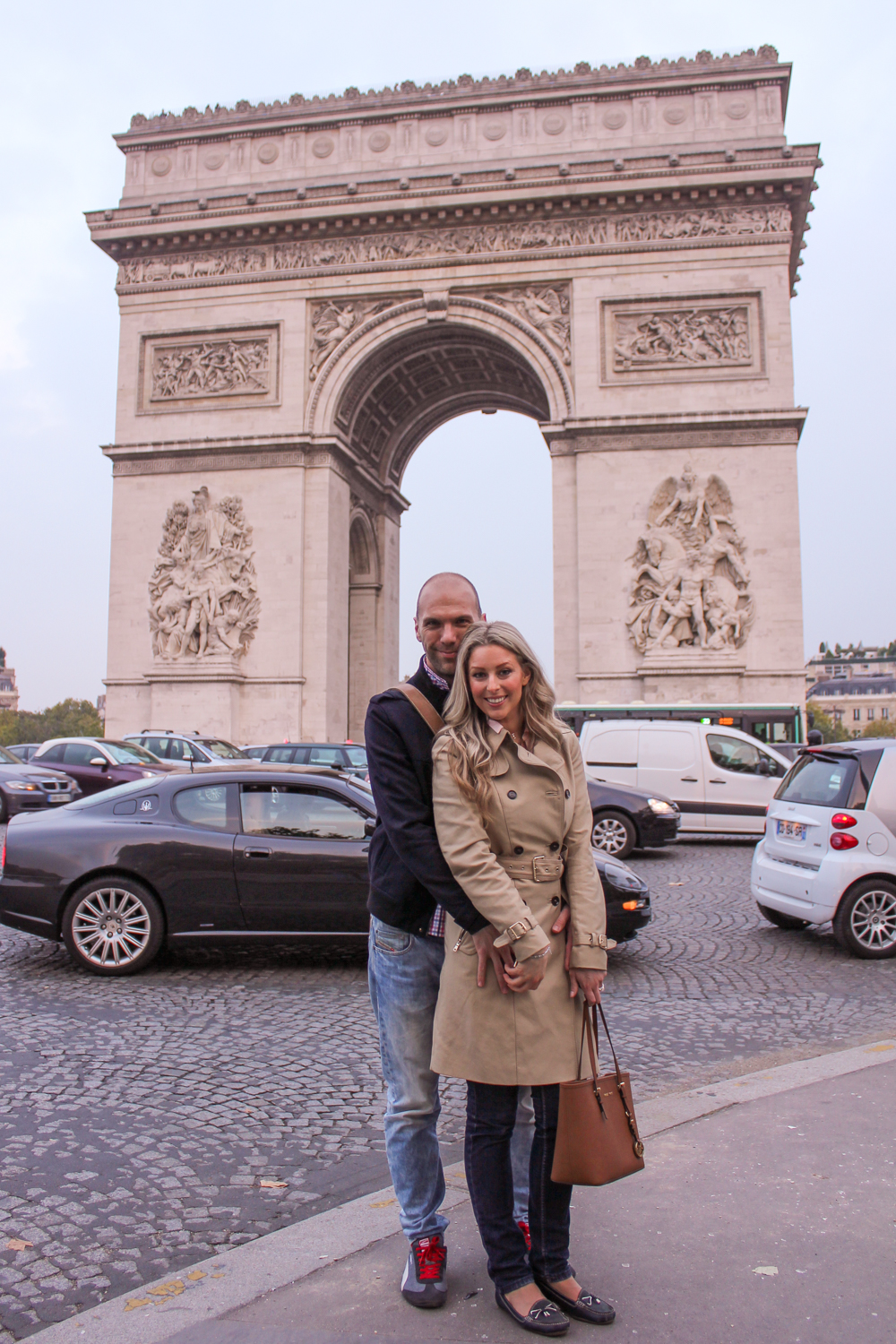 Deneale from Goldfields Girl wearing trench coat and Michael Kors bag in Paris Arc du Triumph
