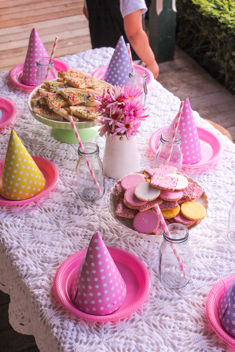 Spring themed kids table with pink polka dot party hats, straws, fairy bread and cookies