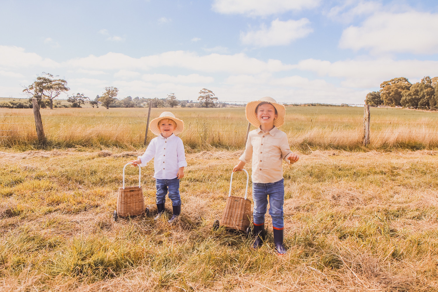 Little boys wearing linen shirts straw hats and Olli Ella luggy at sunflower farm near Ballarat