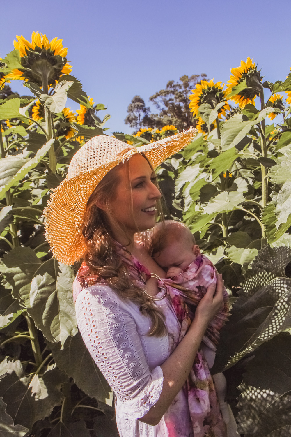 Goldfields Girl at sunflower farm in Ballarat in Victoria. Wearing white eyelet dress, straw hat and ping ring sling baby carrier.