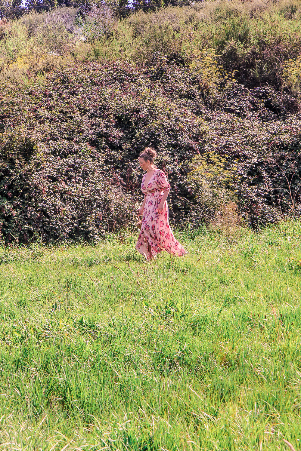 Goldfields Girl wearing pretty red and pin floral dress while blackberry picking