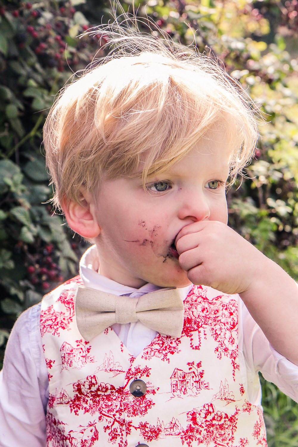 Little boy wearing Janie and Jack bow tie with red toile vest